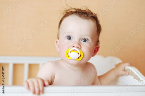 funny baby with dummy in white bed