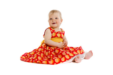 Adorable little baby girl in red dress sitting on floor