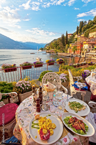 Romantic dinner scene of plated Italian food on terrace overlook - 54953325