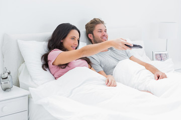 Woman changing tv channel in her bed