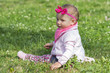 A cheerful baby girl is playing on the grass