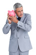 Sceptical businessman holding piggy bank