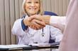 Ärztin und Patient machen Handschlag