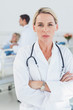 Serious doctor posing with doctor attending patient on backgroun
