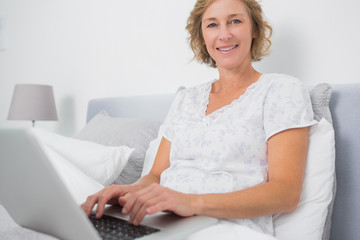 Cheerful blonde woman sitting in bed using laptop