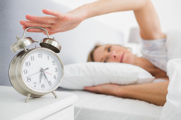 Tired blonde woman turning off her alarm in the morning