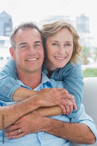 Happy woman hugging her husband on the couch from behind