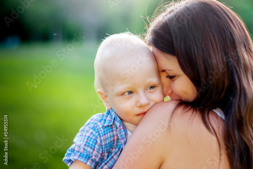 Young Mother and her little son on a nature background