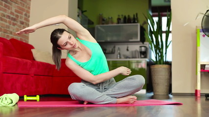 Young woman exercising in home, dolly shot