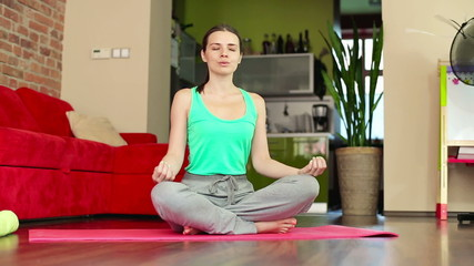 Woman meditating, doing yoga exercise at home, dolly shot