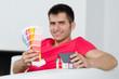 junger mann zeigt farbkarten und haus
