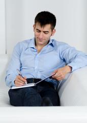 junger mann schreibt in buch