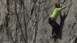 rock climber climbs then pauses to chat to his friend