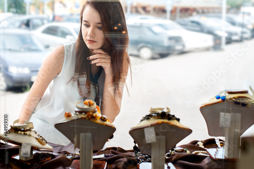 young woman choosing jewelry in shop