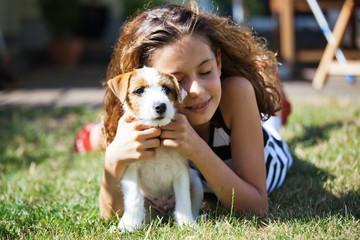hübsches junges Mädchen umarmt ihren Welpen