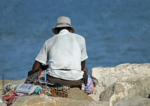 peddler of necklaces and accessories rests on the Pier by the se