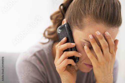 Stressed young woman talking mobile phone