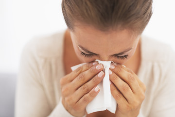 Woman blowing nose into handkerchief