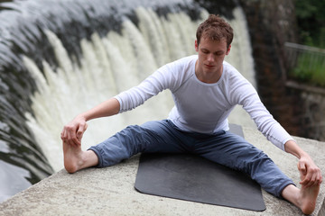 young fit man practicing stretching over waterfall - outdoor