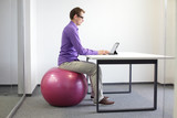 man on stability ball  with tablet - correct sitting position