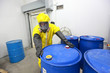 risky job - worker in  uniform rolling barrel wh toxic waste