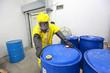 risky job - worker in  uniform rolling barrel wh toxic waste