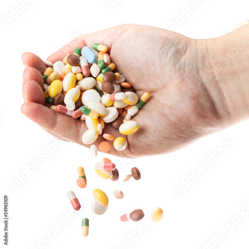 Man's hand holding and dropping a handful of medicine pills