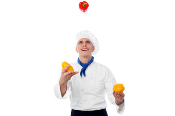 Chef juggling with vegetables