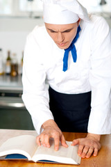 Male chef referring to cooking manual