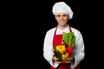 Handsome chef holding vegetables bowl
