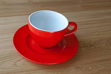 Red empty coffe cup on the oak table
