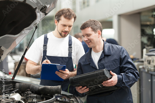 Mechanics at work shop. Two confident mechanics discussing somet