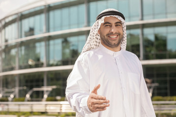 Good deal! Cheerful Arab businessman stretching out his hand and
