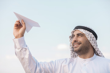 Arab businessman with paper airplane. Cheerful Arab businessman