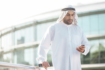 Arab businessman with mobile phone. Confident Arab businessman l