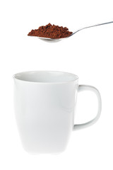 White coffee mug with a teaspoon of granulated instant coffee