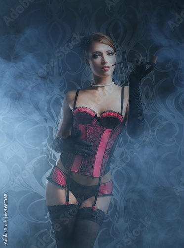 A young redhead woman posing in erotic lingerie on fog