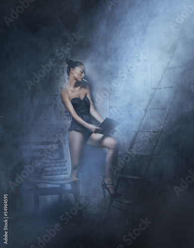 Fashion shoot of a young woman in lingerie reading a book