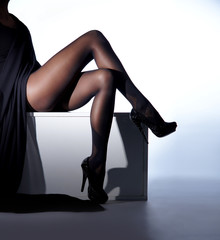 Sexy female legs in black erotic stockings and high heels