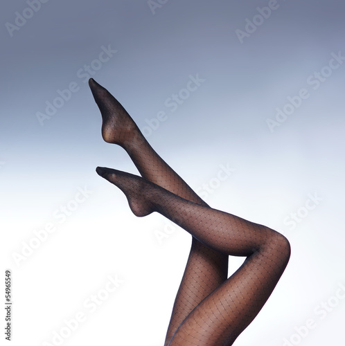 Sexy female legs in black erotic stockings on a blue background