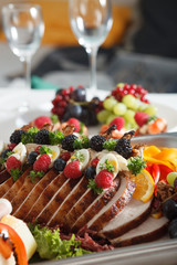 sliced veal on the rib decorated with fruit on silver plate