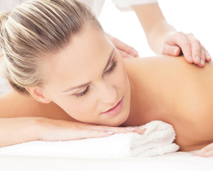 Portrait of a young woman relaxing on a back massage procedure