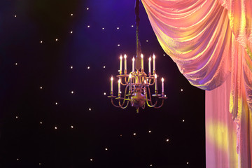 Curtains with yellow lighting and chandelier hanging in theater.