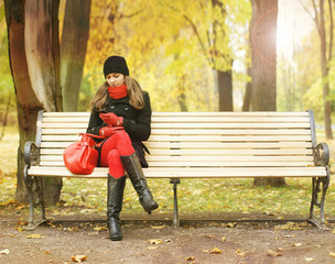 A young woman sitting on a bench in an autumn park