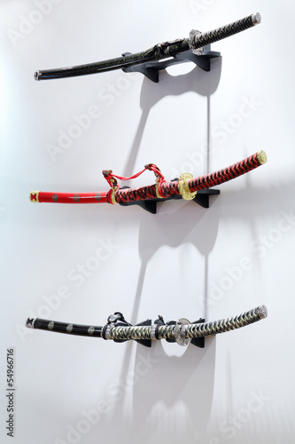 Three samurai swords hang on white wall in Japanese restaurant.