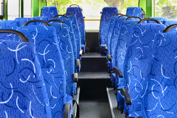 Soft seats for passengers inside saloon of empty city bus