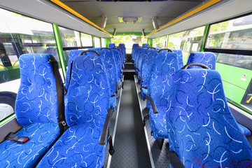 Blue seats for passengers in saloon of empty city bus