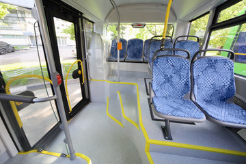 Seats in passenger compartment of empty city bus with big window