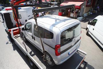 Truck loads fined car on street