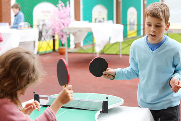 Little girl and boy in blue play table tennis in park